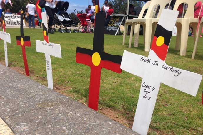 Protesters in central Geraldton behind a row of crosses representing deaths in custody.